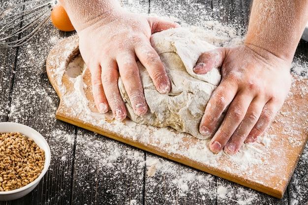 Vista dall'alto della mano del panettiere preparando la pasta con farina sul tagliere