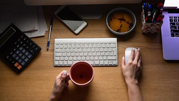 Vista dall'alto della mano della donna che lavora al computer, tenendo la tazza di tè, lavoro da casa di notte. libero professionista.