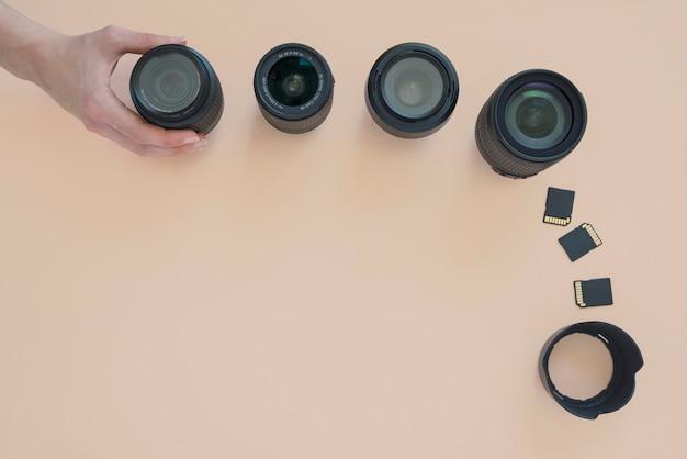 Vista dall'alto della mano della persona che organizza l'obiettivo della fotocamera; scheda di memoria e anelli di prolunga su sfondo colorato