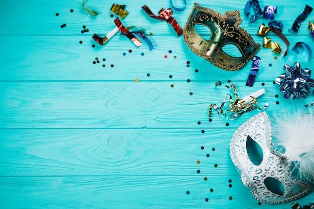 Vista dall'alto della maschera di carnevale di travestimento d'argento e d'oro con decorazioni per feste sul tavolo di legno