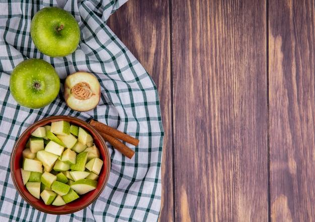 Vista dall'alto della mela intera fresca con fette di mela tritata sulla ciotola con bastoncini di cannella sulla tovaglia controllata e legno con spazio di copia