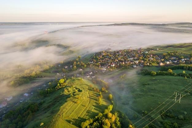 Vista dall'alto della nebbiosa collina erbosa verde, tetti di casa di villaggio nella valle tra alberi verdi sul cielo blu panorama di paesaggio nebbioso di primavera all'alba.