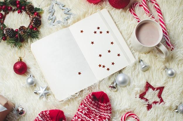 Vista dall'alto della nota di carta per gli obiettivi del nuovo anno e l'elenco delle risoluzioni con decorazioni natalizie