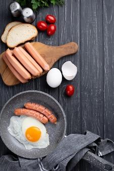 Vista dall'alto della padella con uovo e salsicce per la colazione