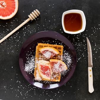 Vista dall'alto della piastra con waffle e agrumi