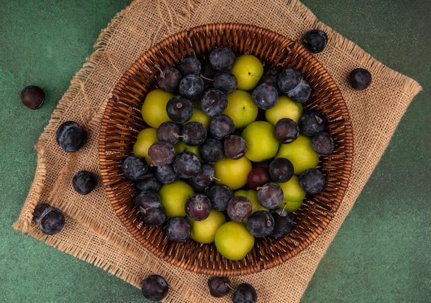 Vista dall'alto della piccola prugnola di frutta blu-nera acida su un secchio con prugna ciliegia verde su un panno di sacco su sfondo verde