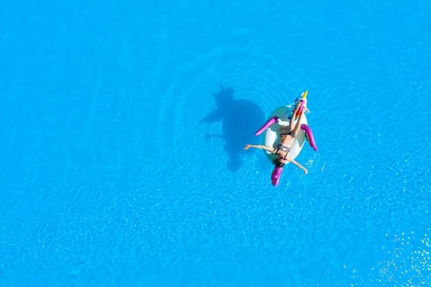 Vista dall'alto della piscina con una ragazza in costume da bagno su un cerchio gonfiabile. rilassarsi e abbronzarsi in estate.