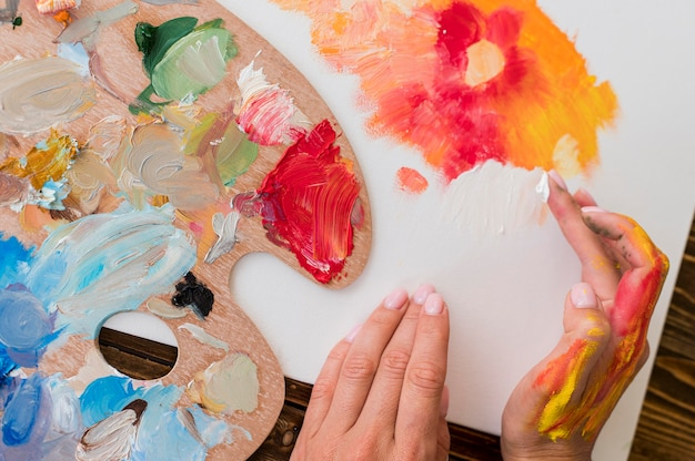 Vista dall'alto della pittura dell'artista usando le mani