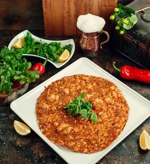 Vista dall'alto della pizza turca lahmacun servita con prezzemolo, limone e ayran