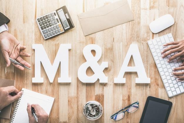 Vista dall'alto della postazione di lavoro aziendale con lettere e lettere di fusione o acquisizione e fusione