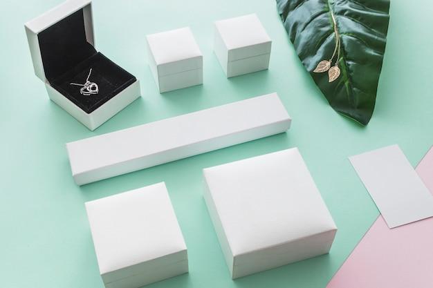 Vista dall'alto della scatola di collana cuore con pacchetti chiusi su sfondo pastello