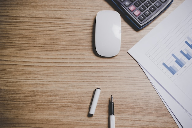 Vista dall'alto della scrivania con la penna, il computer portatile, il ridurre in pani, il mouse, il calcolatore ed il grafico della carta si immergono.