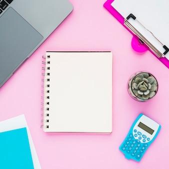 Vista dall'alto della scrivania con quaderno bianco