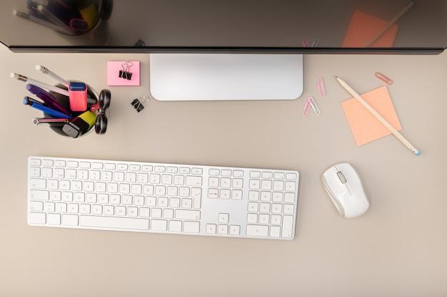 Vista dall'alto della scrivania con schermo del computer, tastiera e altri articoli per ufficio. concetto di lavoro del computer