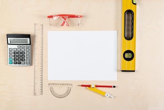 Vista dall'alto della scrivania del costruttore con foglio di carta bianco