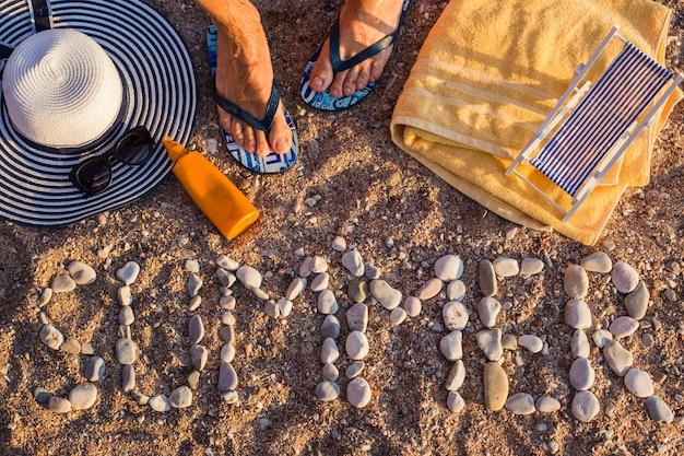Vista dall'alto della spiaggia di sabbia sul mare, gli articoli da spiaggia sono disposti sulla sabbia. la parola estate è di pietra