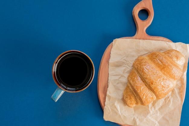 Vista dall'alto della tazza di caffè nero e cornetto su un tagliere e carta artigianale