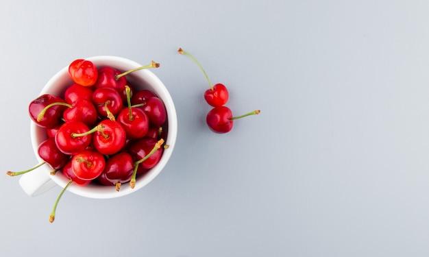 Vista dall'alto della tazza piena di ciliegie rosse sul lato sinistro e superficie bianca con spazio di copia