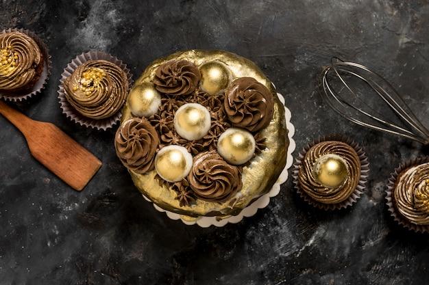 Vista dall'alto della torta con cupcakes e frusta