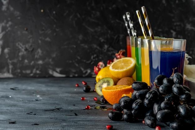 Vista dall'alto della varietà di succo fresco, frutti diversi in giro, copia spazio per il testo su un tavolo nero