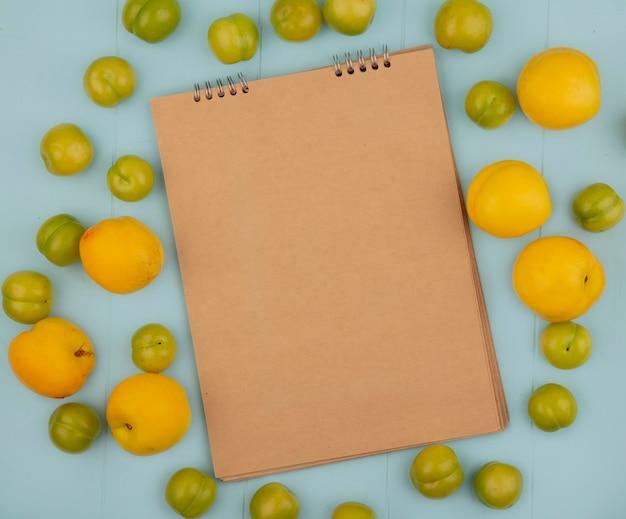 Vista dall'alto della vista dall'alto di fresche deliziose pesche gialle con prugne ciliegia verdi isolate su uno sfondo blu con spazio di copia