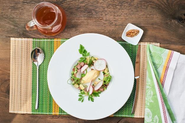Vista dall'alto della zuppa di manzo in un piatto bianco e una brocca di birra su un tavolo di legno