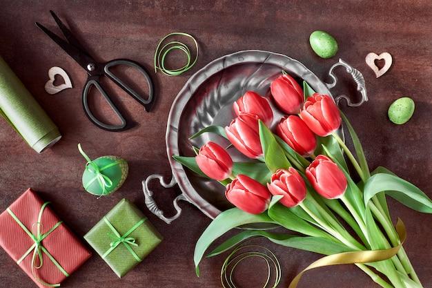 Vista dall'alto delle decorazioni primaverili: regali incartati, fiori di salice e tulipano e cuori di legno