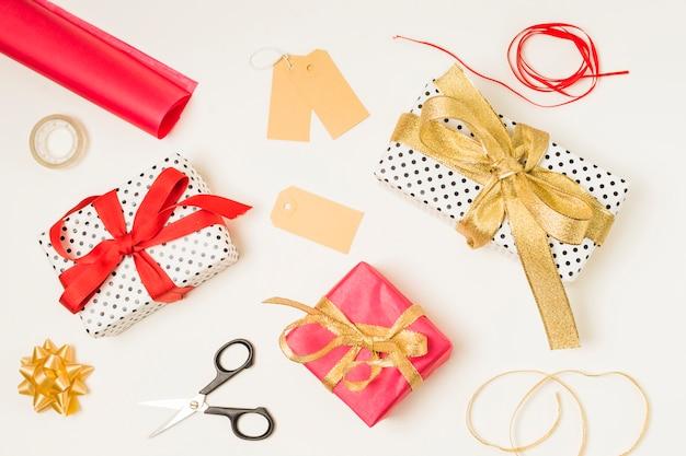 Vista dall'alto delle forniture di cancelleria; scatole regalo e etichette vuote su sfondo bianco