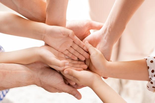 Vista dall'alto delle mani aperte dei bambini piccoli e dei loro giovani genitori che fanno il mucchio come simbolo di solidarietà, amore e affetto