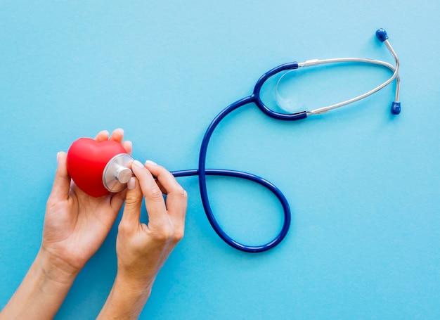Vista dall'alto delle mani che controllano la forma del cuore con lo stetoscopio