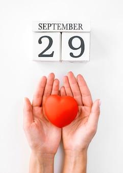 Vista dall'alto delle mani che tengono a forma di cuore con data