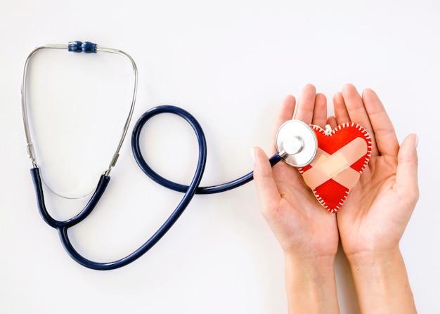 Vista dall'alto delle mani che tengono a forma di cuore danneggiato con lo stetoscopio