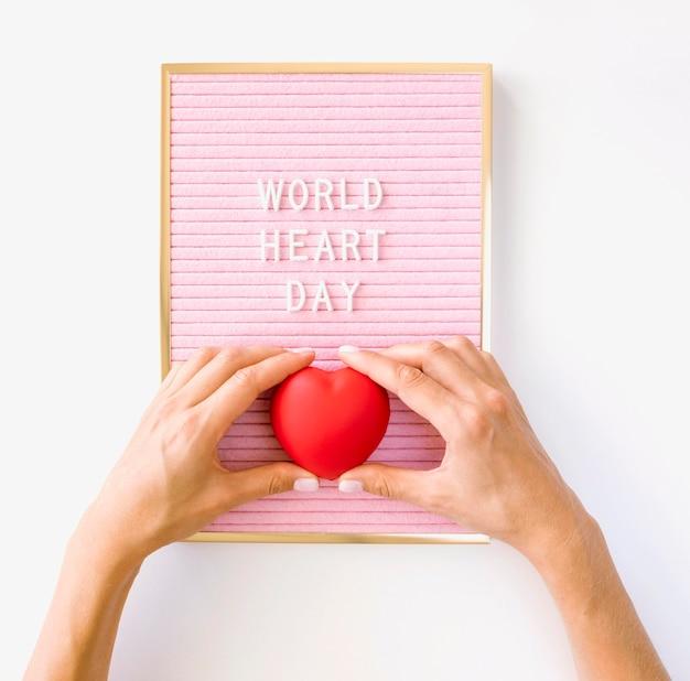 Vista dall'alto delle mani che tengono la giornata mondiale del cuore a forma di cuore