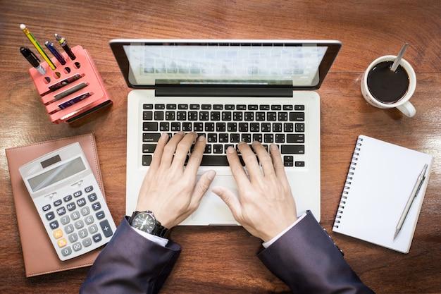Vista dall'alto delle mani dell'uomo di affari che lavora al computer portatile o al ridurre in pani sul banco di legno.