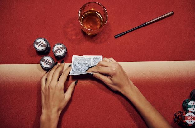 Vista dall'alto delle mani della donna. la ragazza gioca a poker al tavolo da casinò