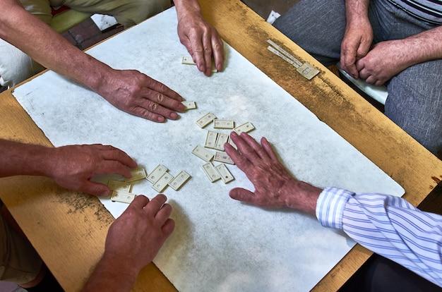 Vista dall'alto delle mani di persone che giocano a domino