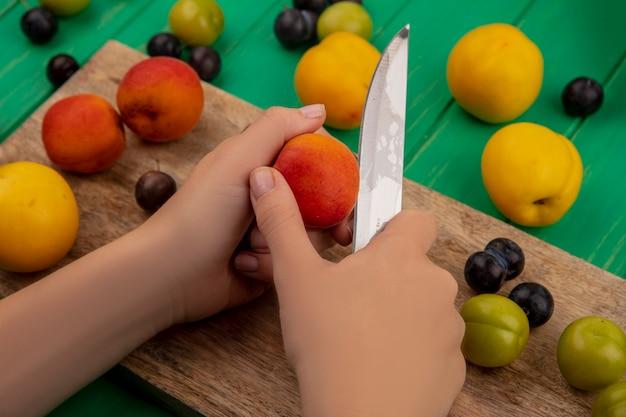 Vista dall'alto delle mani femminili che tagliano la pesca fresca con il coltello su una tavola di cucina in legno su uno sfondo verde