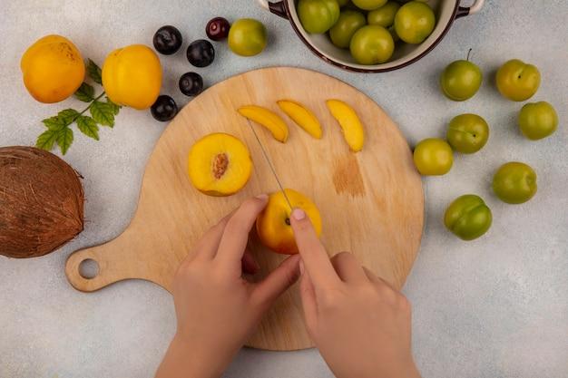 Vista dall'alto delle mani femminili che tagliano la pesca gialla su una tavola di cucina in legno con coltello con cocco con pesche isolato su uno sfondo bianco