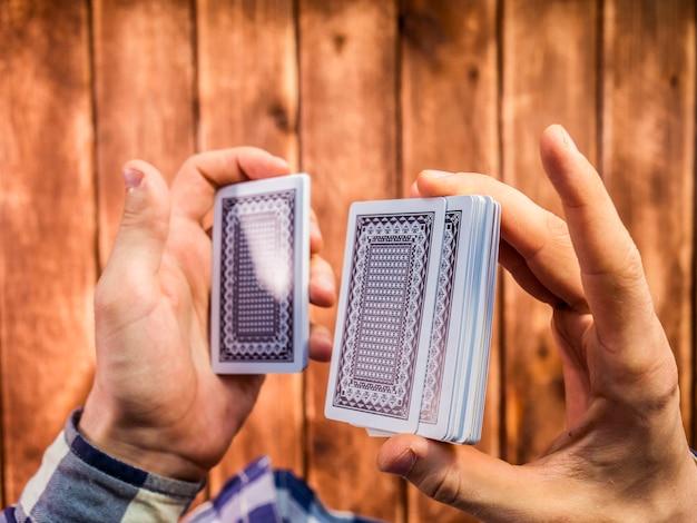 Vista dall'alto delle mani mescolando le carte da gioco sulla superficie in legno