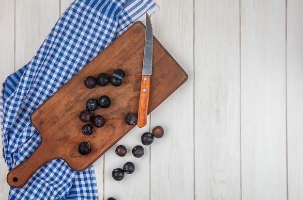 Vista dall'alto delle piccole prugnole blu-nere aspre su un tagliere di cucina in legno con coltello su uno sfondo bianco con spazio di copia