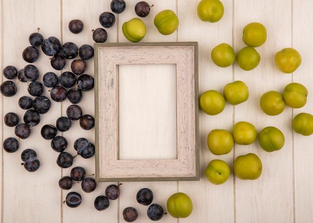 Vista dall'alto delle piccole prugnole di frutta blu-nere acide e prugne ciliegia verdi isolate su un fondo di legno bianco con lo spazio della copia