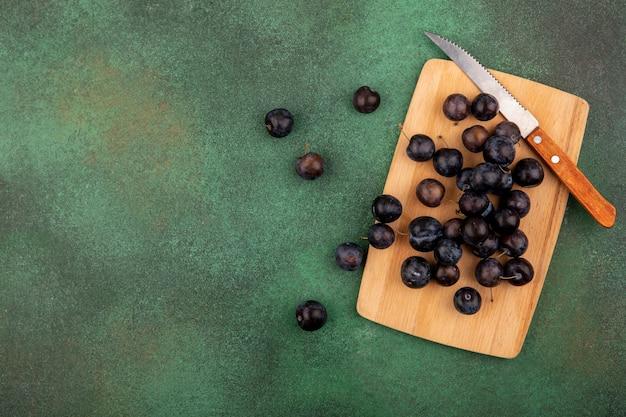 Vista dall'alto delle piccole prugnole di frutta blu-nere acide su un tagliere di cucina in legno con coltello su uno sfondo verde con spazio di copia