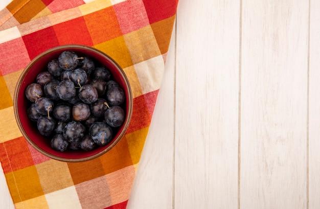 Vista dall'alto delle piccole prugnole di frutta blu-nere acide su una ciotola su una tovaglia a quadri su un fondo di legno bianco con spazio di copia