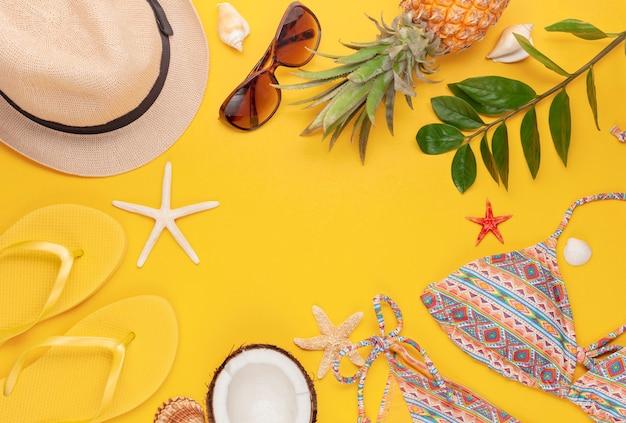 Vista dall'alto di accessori da spiaggia tropicale con costume da bagno, cappello e infradito