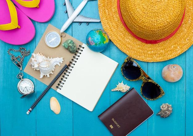 Vista dall'alto di accessori da viaggio sul pavimento di legno chiaro blu della plancia per le vacanze estive