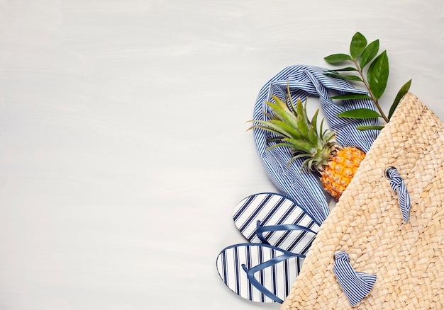 Vista dall'alto di accessori spiaggia tropicale con borsa estiva paglia e infradito