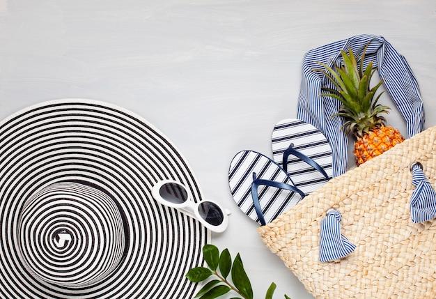 Vista dall'alto di accessori spiaggia tropicale con cappello e infradito