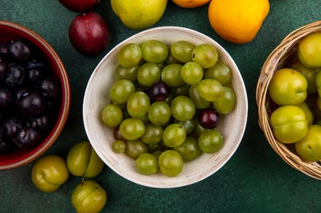 Vista dall'alto di acini d'uva in ciotole con cesto di prugne e prugne nectacot pluots su sfondo verde