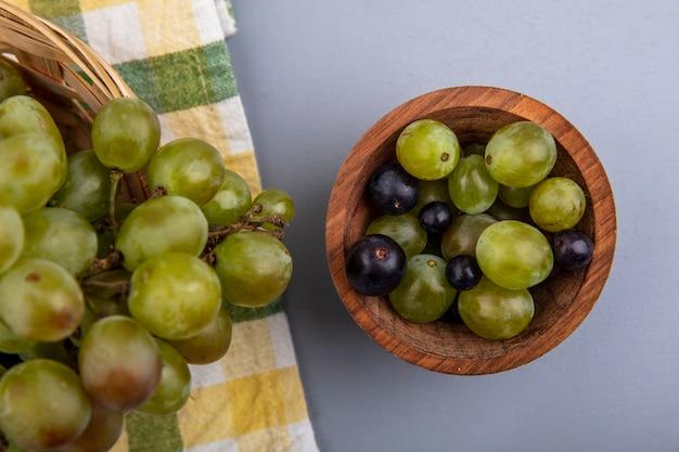 Vista dall'alto di acini d'uva in una ciotola con cesto di uva su un panno plaid e uno sfondo grigio