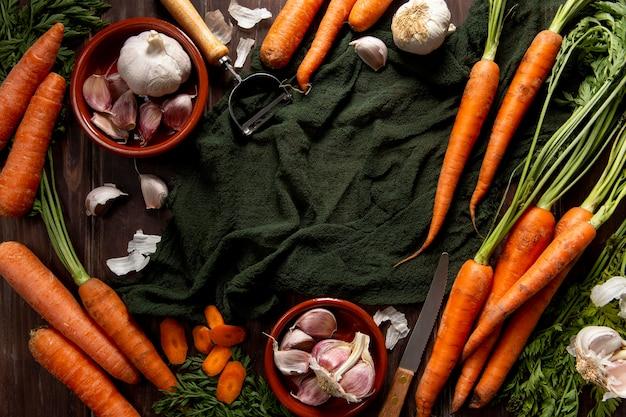 Vista dall'alto di aglio con carote e pelapatate